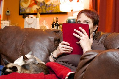 A woman reads her tablet with her two cats beside her. Photo CC-BY Jamie McCaffrey
