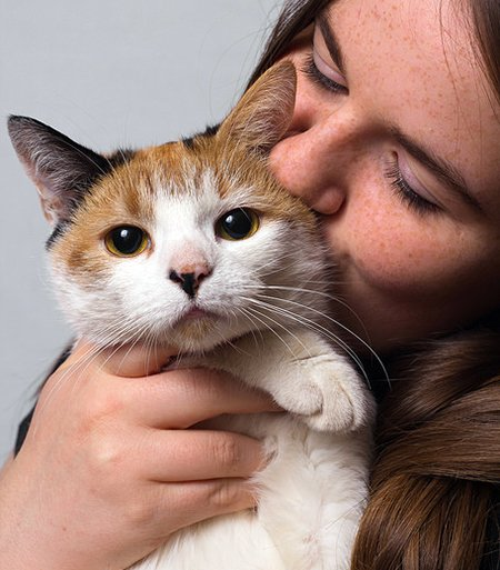 A girl holding and kissing a calico cat