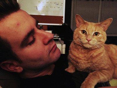 A dark-haired man holds an orange tabby cat