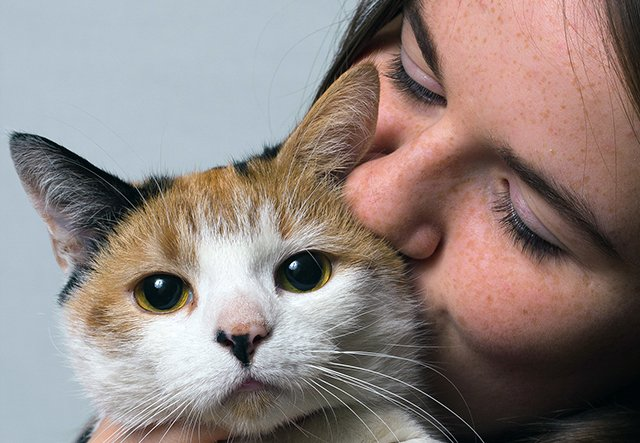 A woman holds a cat